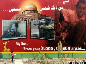 A CHILD STANDS NEXT TO HIZBOLLAH POSTER ON HIGHWAY IN LEBANON.